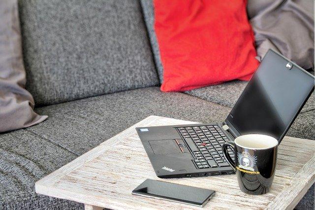 Vertrauen und Technik- die Eckpfeiler in Krisenzeiten Comouter und Kaffeetasse Sofa