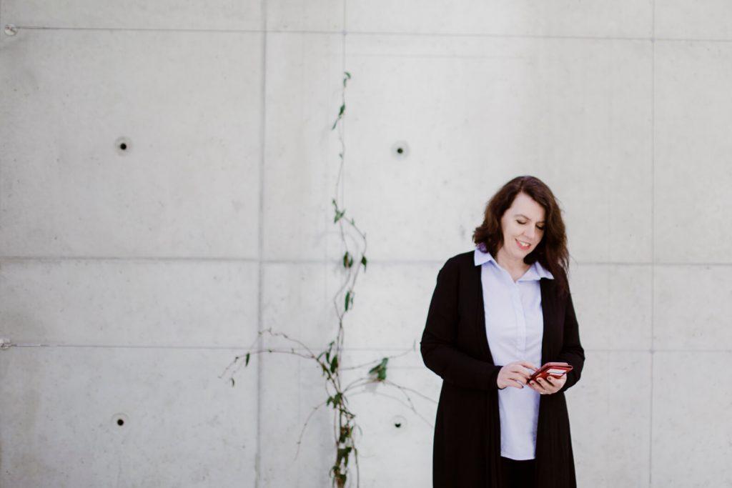 Termin vereinbaren mit Marion Ketteler Strategie Beratung fuer Steuerkanzleien Marion Ketteler mit einem Smartphone vor einer hellen Wand